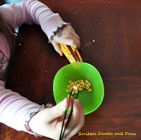 Build fine motor skills by picking corn with tweezers
