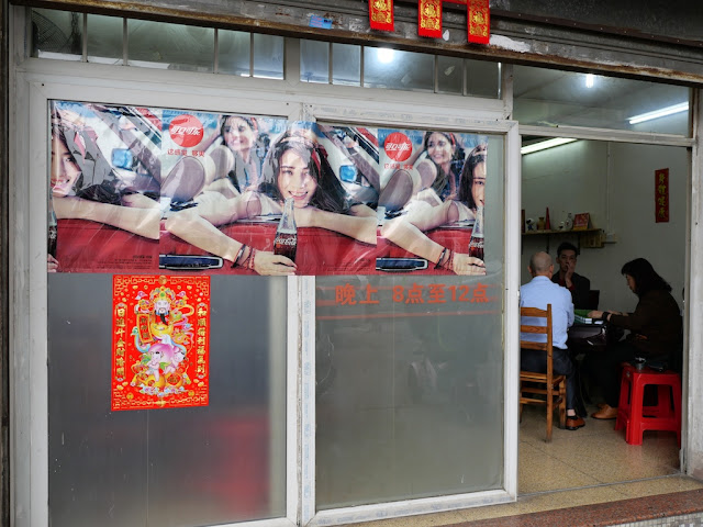 Coca-Cola ad and people playing mahjong in Jiangmen, China