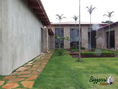 Execução do caminho com pedra tipo cacão de Goiás com junta de grama com os revestimentos de pedra rústica, construção de lagos com as pontes de madeira e a execução do paisagismo com o gramado de grama esmeralda.