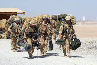 blog picture of soldiers walking along with back packs and other equipment