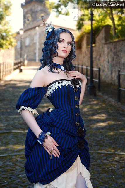 Neo-Victorian Steampunk woman wearing a blue and black striped polonaise dress (corset and attached overskirt that reveal decorative underskirt/petticoats). She has blue hair, a blue fascinator and blue jewelry.