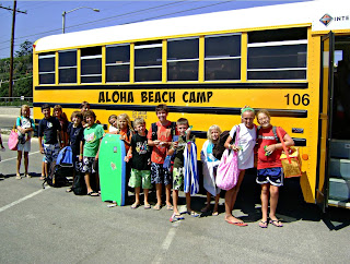 Large group of campers standing in front of Aloha Beach Camp's summer camp bus in the Zuma Beach parking lot.