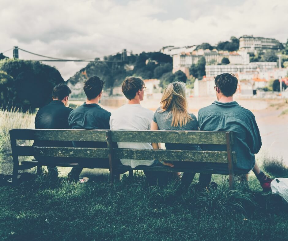 "Five teens sit on a wooden park bench with their backs to the camera. They're all looking towards a city in the distance. A large bridge sits on the left of the photo in the background. There are 3 boys, then a girl, then another boy on the bench. Image for ""Teaching your children about social media""."