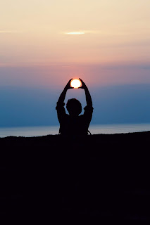 """person """"holding"""" the sun during sunset"""