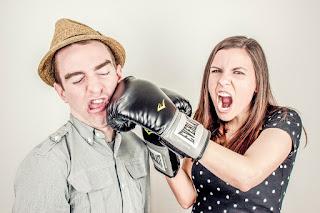 Junge Frau boxt Ihrem Freund mit Boxhandschuhen ins Gesicht