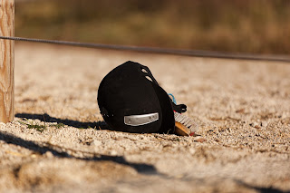 A riding hat upside down on the ground with a grooming brush inside