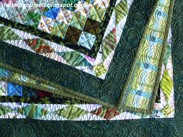 Detail showing green diamond border and free-motion quilting.
