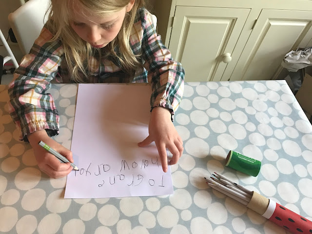 "M is still writing the letter with the write size pencil. The Froot colouring pencil box is open next to her. She has written ""To Grane howow ar you"""