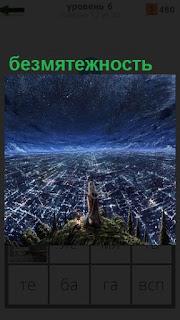 Девушка на вершине смотрит на город в огнях, безмятежность и спокойствие души