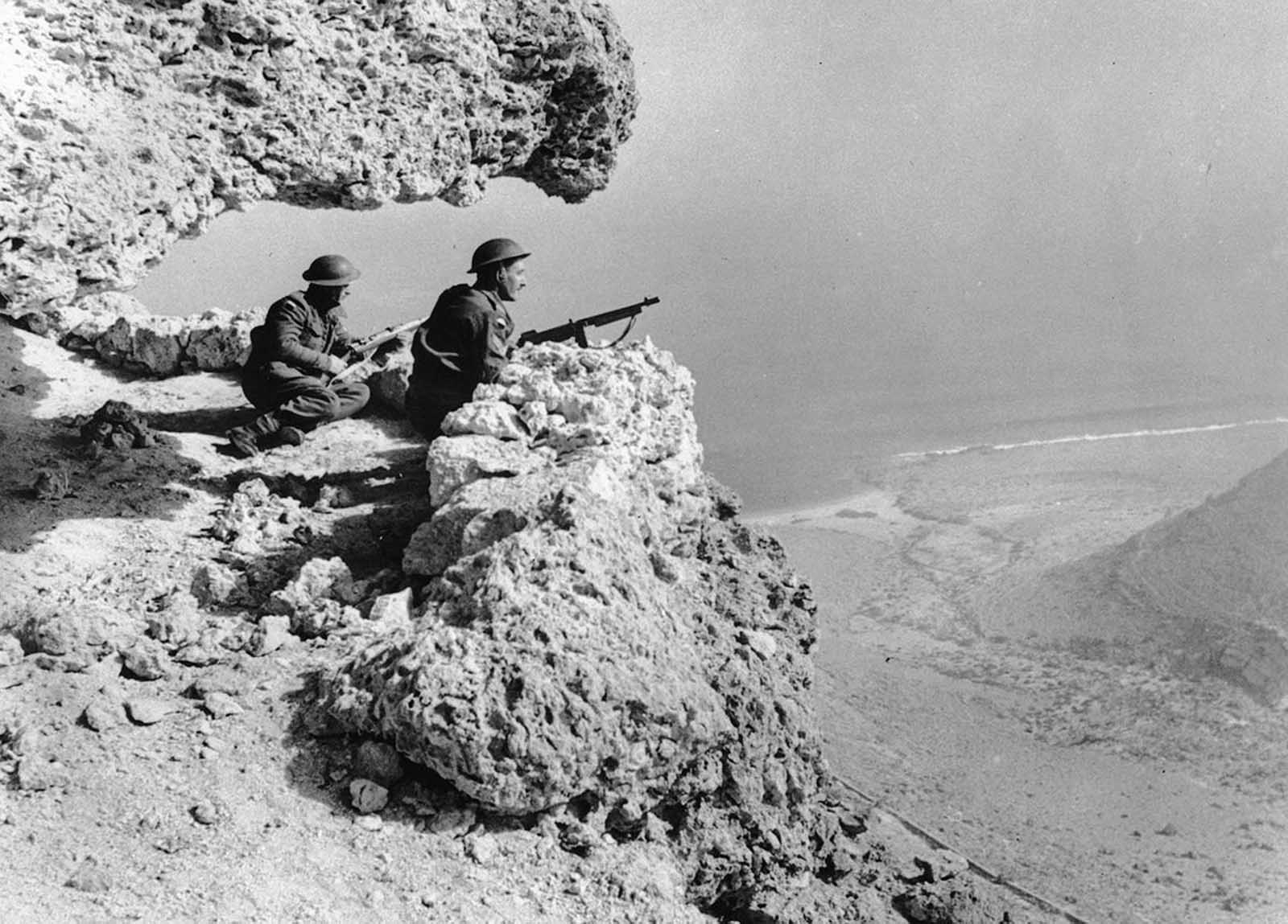A British patrol is on the lookout for enemy movements over a valley in the Western Desert, on the Egyptian side of the Egypt-Libya border, in February of 1942.