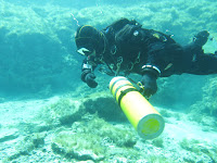 Sidemount diver unclips the rear of cylinder for skills practice