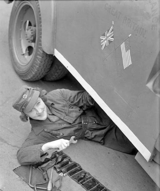 Women of the WW2 MTC - Mrs Pat Macleod slides out from under the ambulance she is repairing to smile for the camera. She is doing maintenance work on ambulance 8, which was presented by Elliott Nugent Esq. through the American Field Service.
