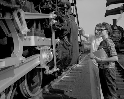 Man and woman inspect a steam locomotive