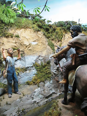 Diorama of a 19th-century man standing in the bush with his hands up,in front of a Maori on a horse.