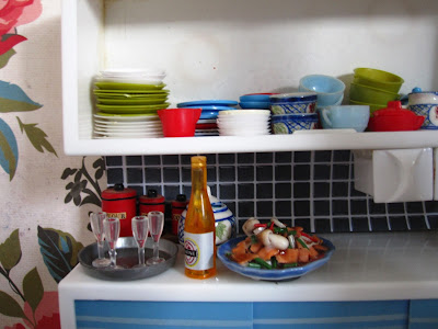 One-twelfth scale modern miniature kitchen dresser filled with mismatched crockery and holding a tray of champagne glasses, a bottle of sparking wine and a platter full of seafood.