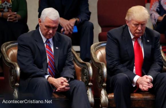 Mike Pence orando junto a Donald Trump