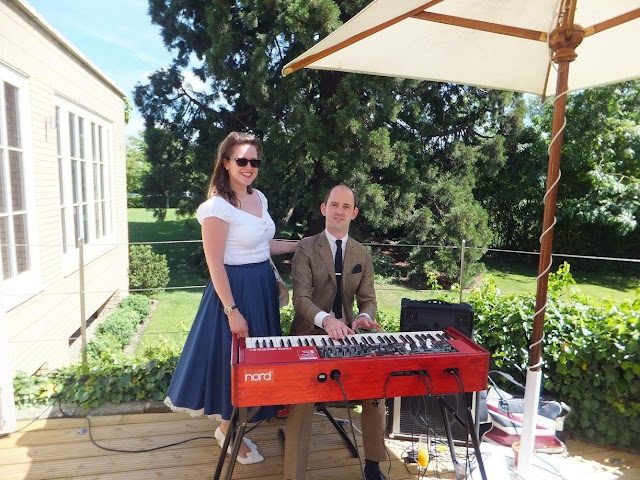 Woman standing with Man in suit playing Nord Electro 5D keyboard on decking at outdoor British wedding