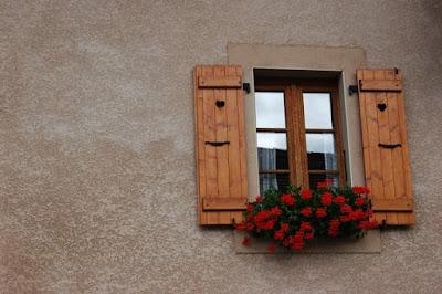 Une façade de maison avec une fenêtre aux volets battants ouverts.