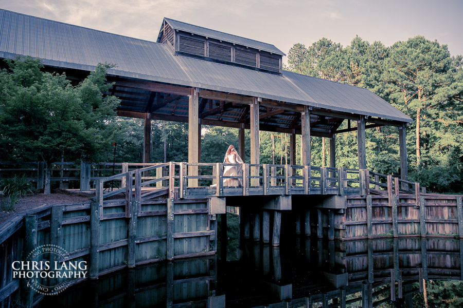 Image of a bride standing underneath the covered bridge at River Landing.  Awesome bridal photos