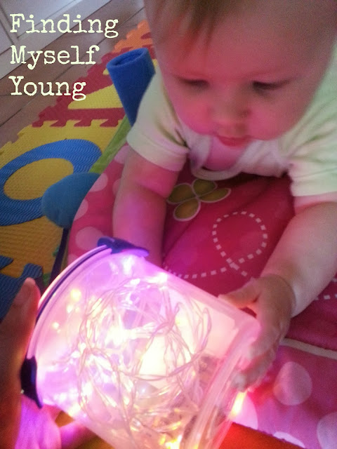 Baby rolling a light filled container on the ground during tummy time.