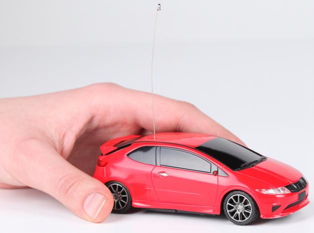 Une main déplace une voiture miniature rouge.