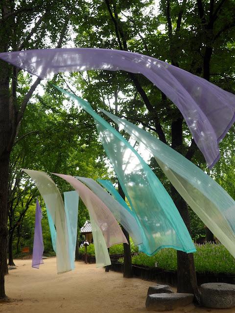 Colourful fabrics hanging between trees in the Korean Folk Village, Yongin, Gyeonggi-do, South Korea