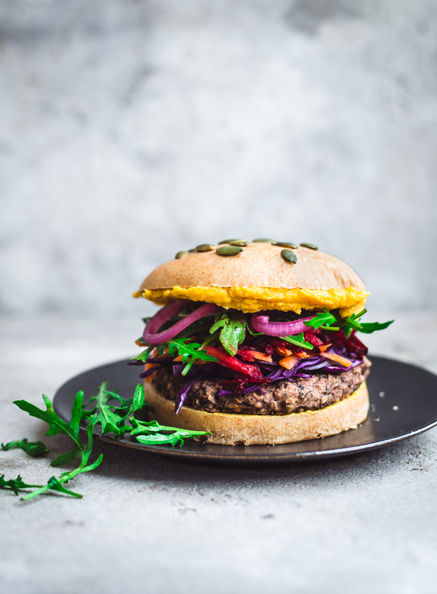 Vegan and gluten free black bean burgers with rice for a solid, easy to handle veggie burger. Topped with a rainbow of winter vegetables including pickled onions and shredded root vegetables.