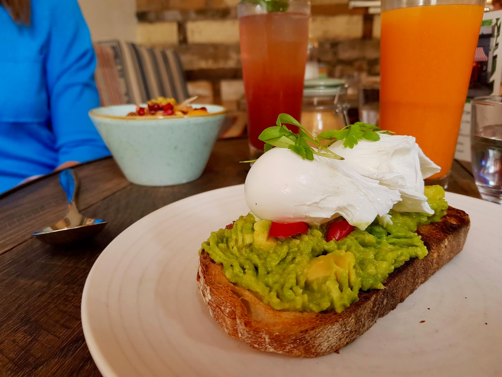 plates of avocado on toast and fruit granola on a table in a cafe