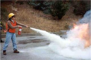 wanita menyemprot tabung pemadam kebakaran