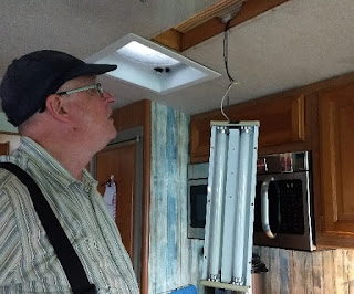 man looking at old RV light fixture hanging from ceiling