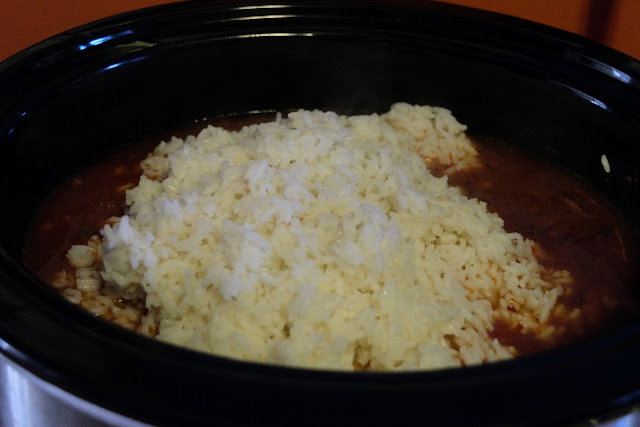The cooked rice being added to the crockpot.
