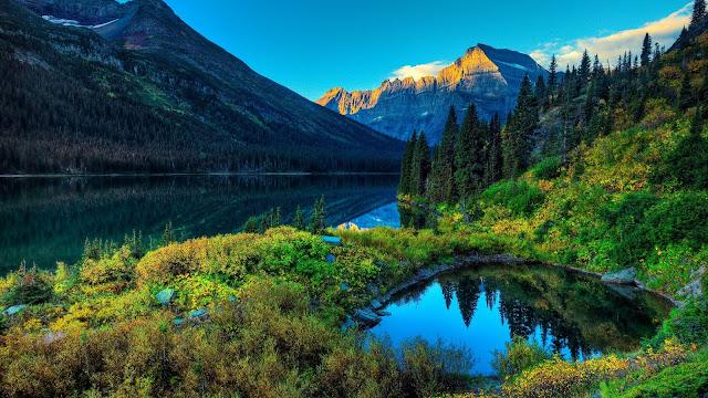 Prachtige wallpaper met een meer in de bergen. De bomen weerspiegelen in het water.