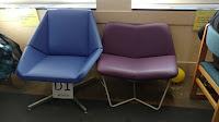 A blue cushioned chair and a purple cushioned chair.