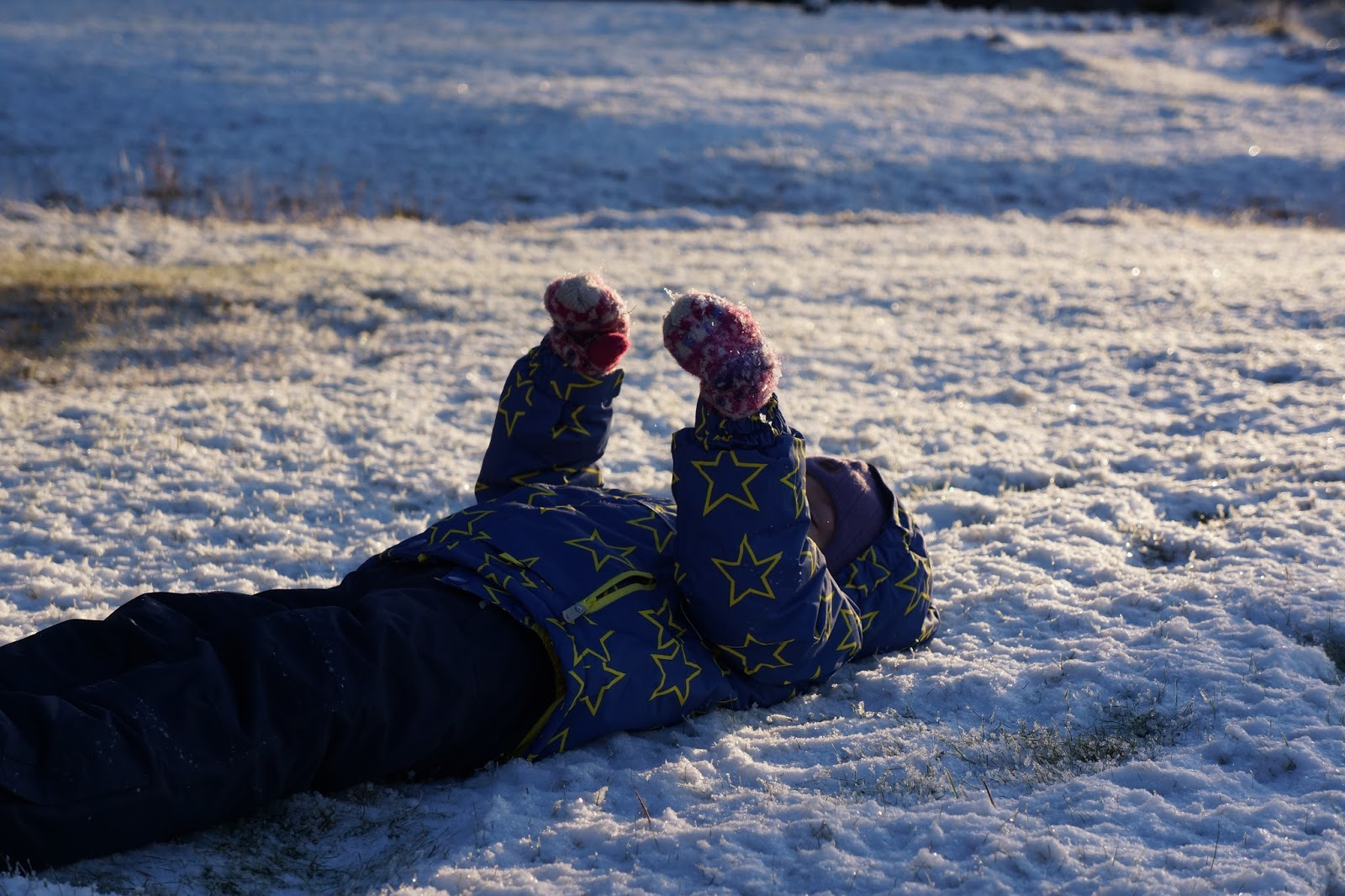 a child lying in snow wearing ski clothing