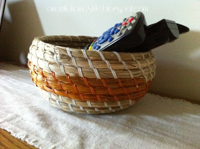 Round basket with orange stripe to hold remote controls