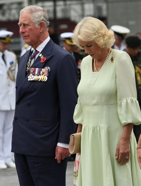 Britain's Prince Charles, Prince of Wales (L) and Camilla, Duchess of Cornwall observe a minute of silence during a wreath laying ceremony at The Cenotaph war memorial in Singapore on October 31, 2017.