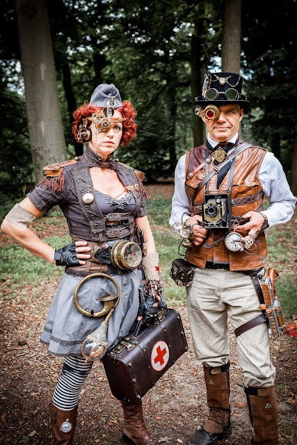steampunk couple. the female is a nurse or medic and the man is a photographer with a brownie camera. Lots of mechanical gadgets, monocles, goggles and gauges