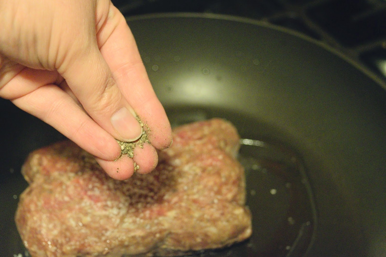 Ground beef in the pan being seasoned with pepper.