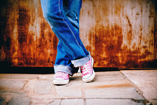 legs in jeans from lower thigh down, wearing pink shoes and in front of a rusty wall