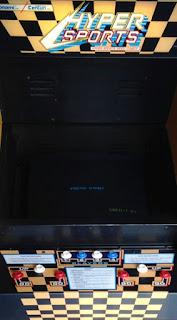 Detalle de una máquina de Konami Hyper Sports. La imagen muestra la pantalla (insert coin), tres botones de acción para cuatro jugadores, dos a dos como máximo
