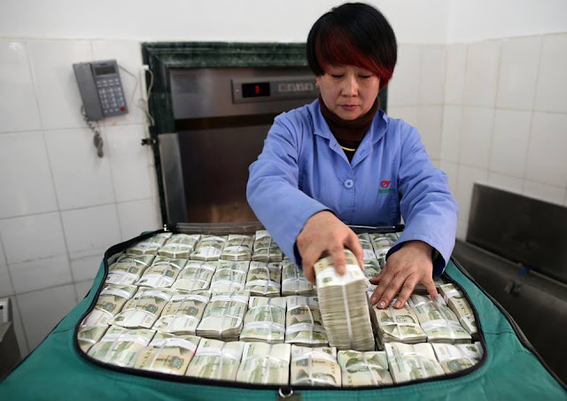 Workers count piles of change for bus company in Kunming