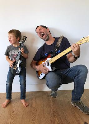 Padre e hijo cantando con guitarra eléctrica