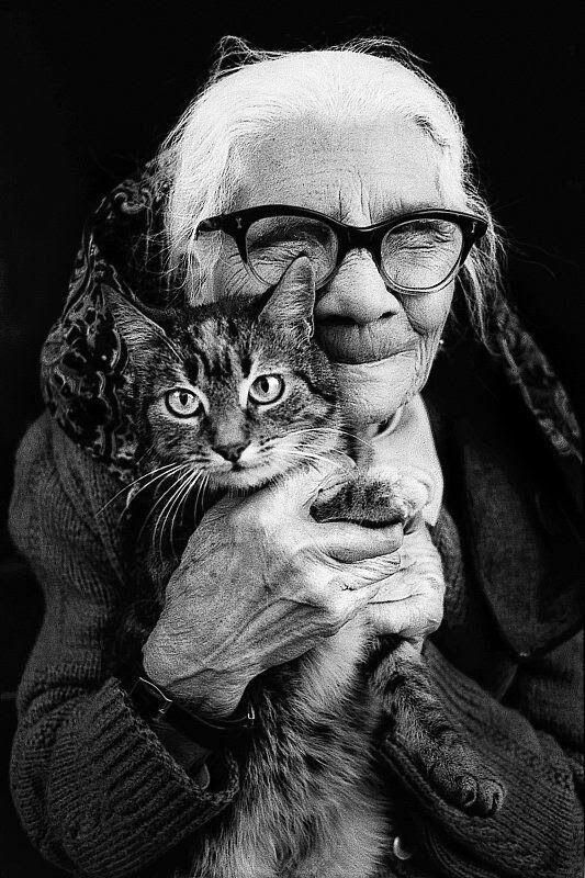 Beautiful black and white photo. Senior woman with white hair and cateye glasses, hold a kitten to her cheek and smiles