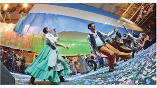 A woman in a full green skirt, white blouse, and blue apron, and a man in brown trousers, a light blue shirt, and a dark blue vest are folk-dancing in a convention center. The picture is taken from ground level looking up, and the Argentinian and Welsh flags hang from the ceiling behind them.