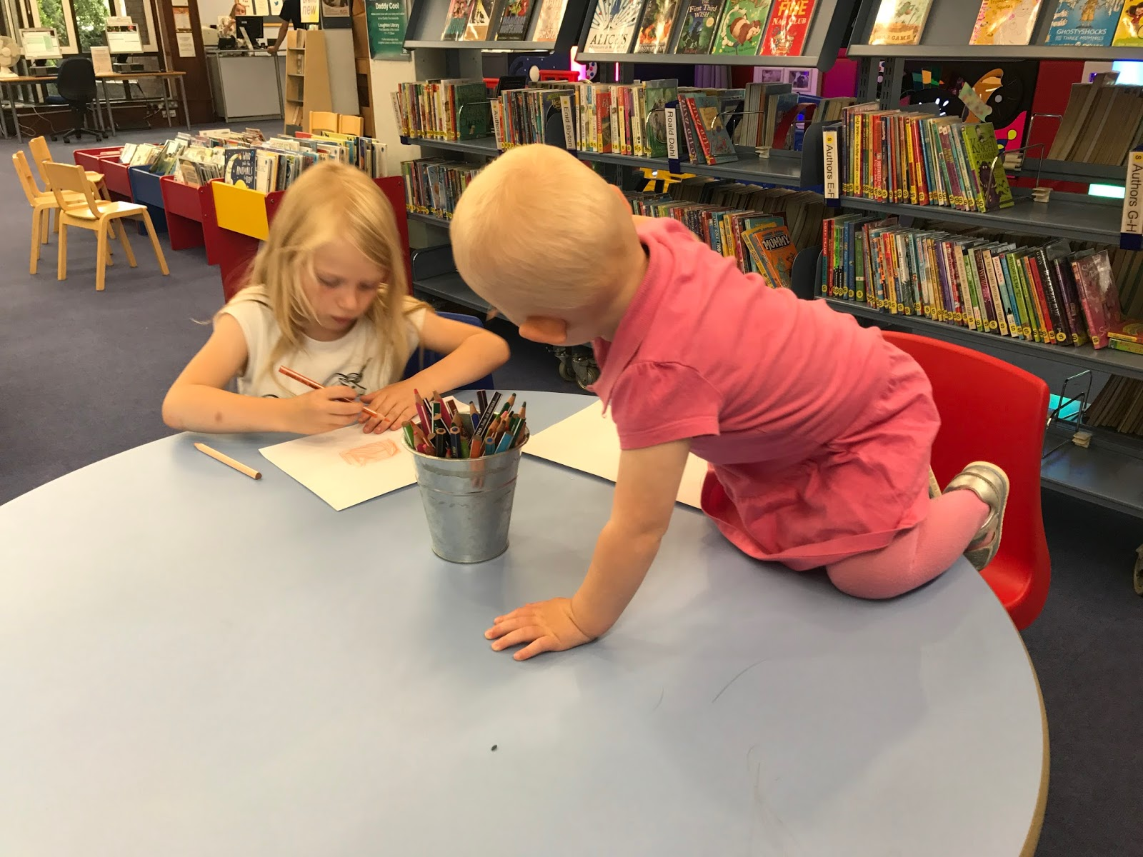 A girl drawing in a library while the toddler climbs on the table