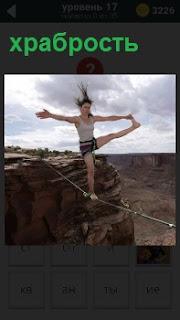 Девушка на одной ноге на проволоке над пропастью испытывает свою храбрость, поднимая одну ногу в сторону