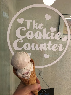 Photo of a double scoop of ice cream from The Cookie Counter vegan ice cream shop in Seattle, WA. Photo taken in front of their entry door with their logo on the glass. https://trimazing.com/
