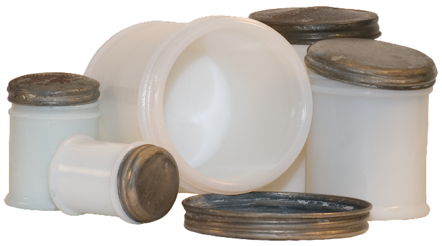 A variety of milk glass jars with tin lids, some small, some large, and one open.