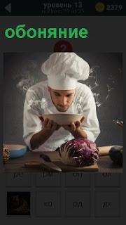 Повар держит в руках тарелку с супом в процессе обоняния своего творения