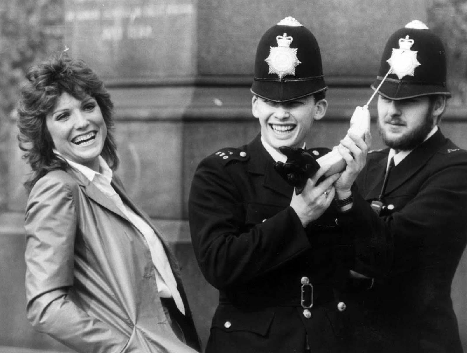A atriz britânica Suzanne Danielle compartilhando uma piada com dois policiais enquanto examinam um dos celulares recém-legais no Reino Unido. 1983.